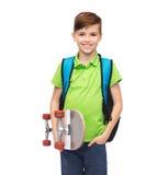 Muchacho stdent feliz con la mochila y el monopatín Foto de archivo libre de regalías