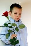 muchacho tímido que da las flores Imagenes de archivo