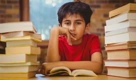 Muchacho tensado que se sienta con la pila de libros Foto de archivo
