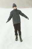Muchacho tranquilo que camina en una trayectoria durante nevada Fotos de archivo