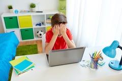 Muchacho trastornado del estudiante con el ordenador portátil en casa Fotos de archivo libres de regalías