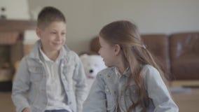 Muchacho travieso adorable del hermano gemelo del retrato que juega tirando del pelo de su hermana linda y sonriendo en sala de e almacen de metraje de vídeo