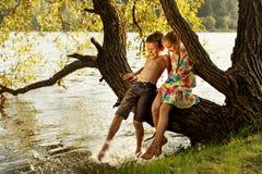 Muchacho travieso y muchacha que se sientan en una rama sobre el agua, riendo, teniendo hablar de la diversión fotografía de archivo libre de regalías
