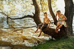 Muchacho travieso y muchacha que se sientan en una rama sobre la pesca del agua, riendo, teniendo hablar de la diversión imagen de archivo