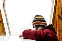 Muchacho triste cerca de la ventana Fotos de archivo