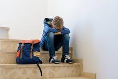 Muchacho triste con la mochila que se sienta solamente en la esquina en la escalera imagenes de archivo