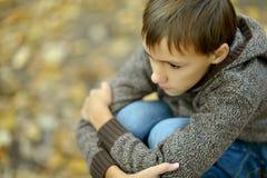 Muchacho triste en parque del otoño Foto de archivo