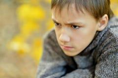 Muchacho triste en parque del otoño Fotografía de archivo libre de regalías