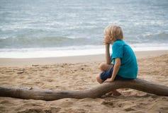 Muchacho triste joven que piensa en la playa Foto de archivo libre de regalías