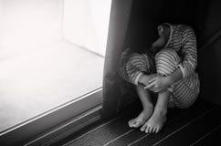 Muchacho triste joven que se sienta en el piso Imagen de archivo