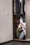 Muchacho triste, ocultando en el armario Imagen de archivo
