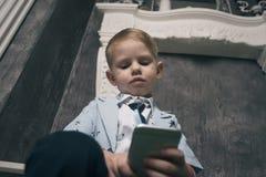 Muchacho triste que mira el teléfono móvil con Fotos de archivo