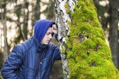 Muchacho triste que se inclina en un árbol Imagen de archivo libre de regalías