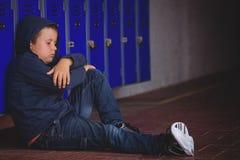 Muchacho triste que se sienta en el pavimento por los armarios Fotos de archivo