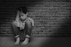 Muchacho triste que se sienta en el piso Foto de archivo