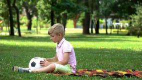 Muchacho triste que se sienta en parque con el fútbol, falta de amigos, víctima de tiranizar foto de archivo