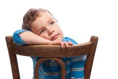 Muchacho triste que se sienta en silla Fotografía de archivo