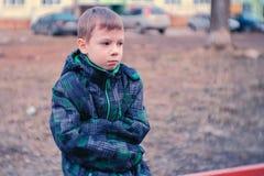 Muchacho triste que se sienta en un banco Pierden y el esperar al muchacho los padres imágenes de archivo libres de regalías