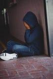 Muchacho triste que se sienta por la pared en pasillo Fotografía de archivo libre de regalías