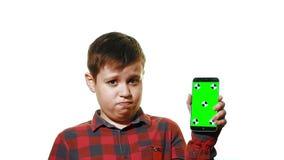 Muchacho triste que sostiene un smartphone en su mano con una pantalla verde almacen de metraje de vídeo