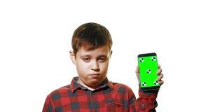 Muchacho triste que sostiene un smartphone en su mano con una pantalla verde almacen de video