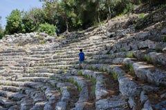 Muchacho turístico que camina en strairs del anfiteatro antiguo en fases fotos de archivo libres de regalías