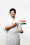 Muchacho u hombre hermoso indio en el desgaste étnico blanco que sostiene la bandera nacional india y que muestra el patriotismo, fotos de archivo libres de regalías