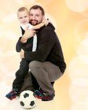 Muchacho, un papá, y un balón de fútbol Foto de archivo libre de regalías