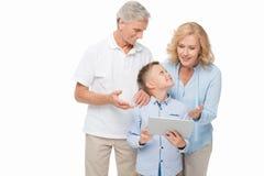 Muchacho y abuelos con la tableta Fotografía de archivo libre de regalías