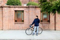 Muchacho y bici jovenes en la ciudad Foto de archivo