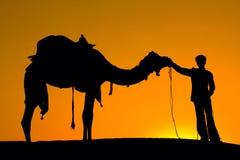 Muchacho y camello de la silueta en la puesta del sol Fotografía de archivo