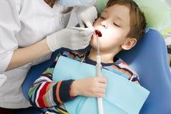 Muchacho y dentista durante un procedimiento dental Imagen de archivo libre de regalías
