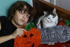 Muchacho y gato del adolescente con la calabaza de la decoración de Halloween y la piedra del sepulcro Foto de archivo