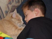 Muchacho y gato durmientes Foto de archivo