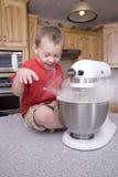 Muchacho y harina en mezclador Foto de archivo
