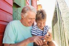 Muchacho y hombre sonrientes que usa el teléfono elegante mientras que se sienta por la pared Foto de archivo