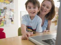 Muchacho y madre felices con el ordenador portátil que se sienta en la tabla Fotos de archivo