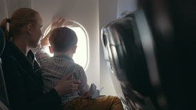 Muchacho y madre que miran afuera a través del avión almacen de video