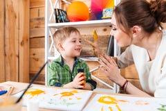Muchacho y madre que se divierten con sus manos pintadas Foto de archivo