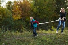 Muchacho y mamá que tiran de la cuerda en naturaleza en el bosque del otoño Fotografía de archivo libre de regalías