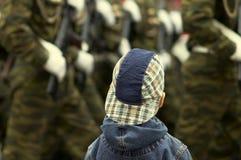 Muchacho y militares en el desfile imagenes de archivo