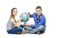 Muchacho y muchacha adolescentes con el globo de la tierra Fotografía de archivo