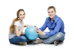 Muchacho y muchacha adolescentes con el globo de la tierra Fotos de archivo libres de regalías