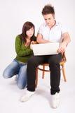 Muchacho y muchacha adolescentes con la computadora portátil Imágenes de archivo libres de regalías