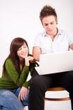 Muchacho y muchacha adolescentes con la computadora portátil Fotografía de archivo libre de regalías