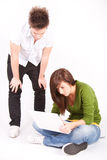 Muchacho y muchacha adolescentes con la computadora portátil Fotografía de archivo