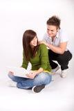 Muchacho y muchacha adolescentes con la computadora portátil Fotos de archivo