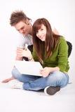 Muchacho y muchacha adolescentes con la computadora portátil Fotos de archivo libres de regalías