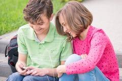 Muchacho y muchacha adolescentes con los auriculares Foto de archivo libre de regalías