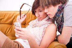 Muchacho y muchacha adolescentes con un teléfono Imágenes de archivo libres de regalías